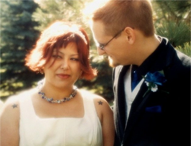 this was taken at our wedding. ed is telling me to behave myself, and i am watching my mother tell a crowd of strangers inappropriate things.